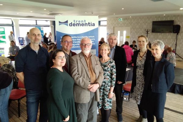 Board of Trent Dementia Trustees Tom, Karen, Justine, James, Michael, Helen, Simon, and the administrator Ghazal with the new banner at the Life with Dementia event.